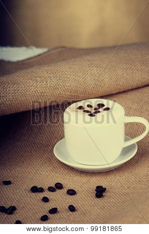 Coffee cup and coffee beans on burlap sack