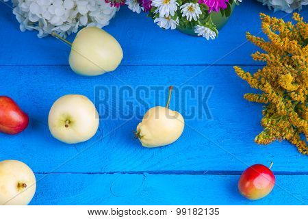Apples, plums and flowers on a table