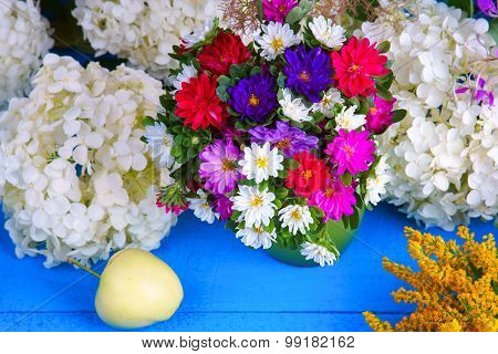 Mixed flowers with apple on a wooden table