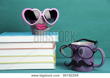Books and cup with mustache and lips on colorful background