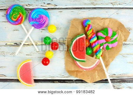 Sweet candies on paper with rustic wood background