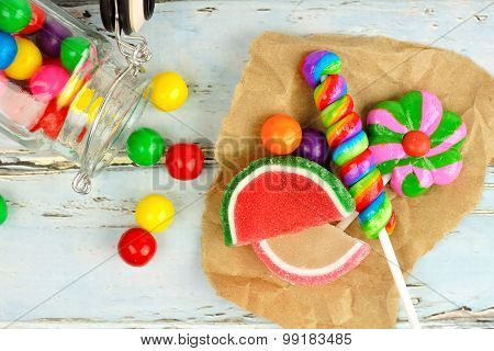 Sweet candies and spilling jar with rustic wood background