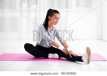 Fit woman doing aerobics gymnastics stretching exercises her leg and back to warm up at home on yoga