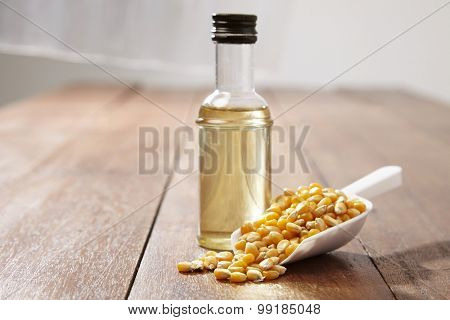 maize corn and bottle of corn oil on wooden table