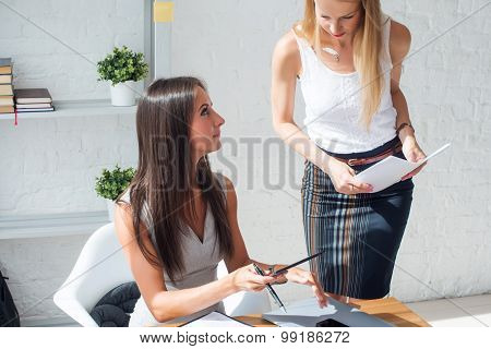Businesswoman talking and showing something to colleague in office