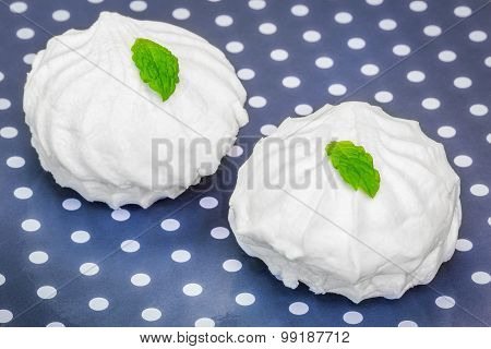 White marshmallows with peppermint on polka cardboard