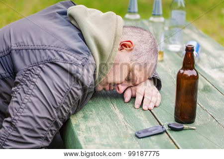 Drunken men near bottles of alcohol at outdoor