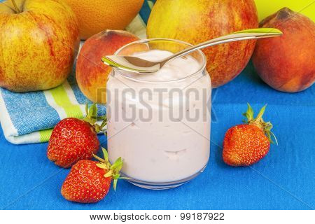 Fresh strawberry yogurt with fruits around on the table