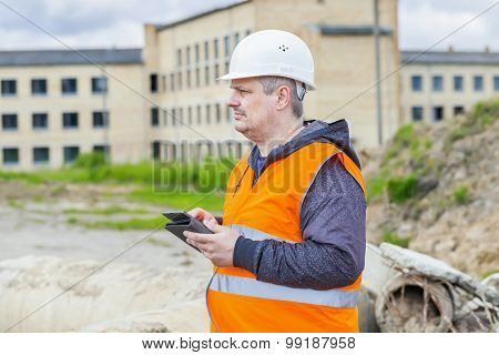 Construction Engineer with tablet PC near building