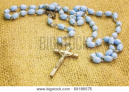 Rosary on rustic jute fabric
