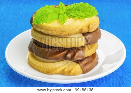 Cookies with mint leaves on white plate