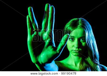 Beautiful Young Woman In Green Light Showing The Alien Sign