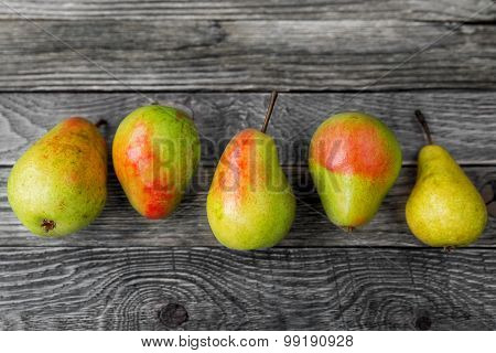 Five Pears Lie In A Row On A Wooden Background. Rustic Cozy Background With Healthy Food.