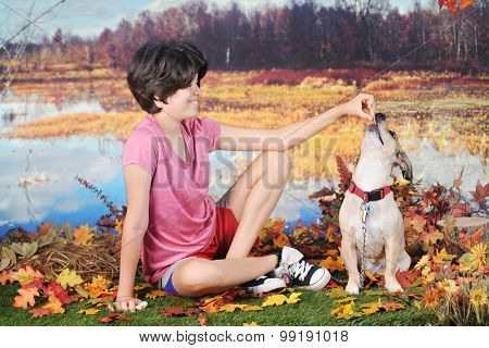 A attractive young teen rewarding her dog with a treat as they play on a warm fall day by the edge of a pond.
