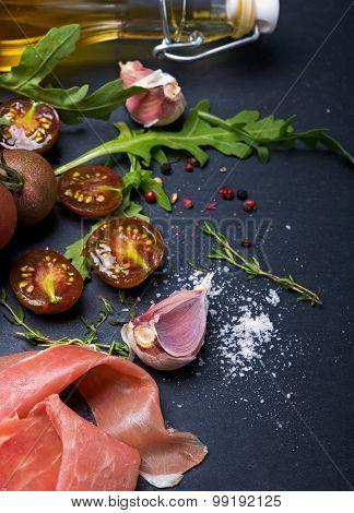 Cherry Tomatoes, Prosciutto, Arugula And Spices On Black Board