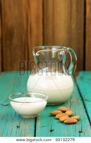 Homemade Fresh Almond Milk In Glass Jar And Glass Bowl And Whole Almonds On Shabby Turquoise Wooden