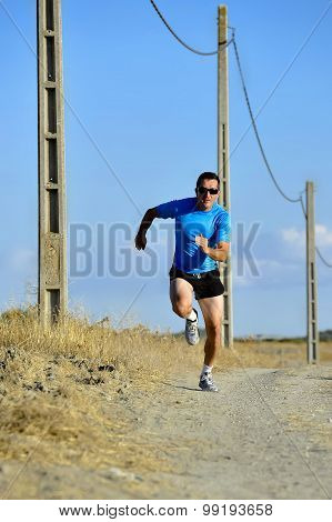 Sport Man With Sun Glasses Running On Countryside Track With Power Line Poles