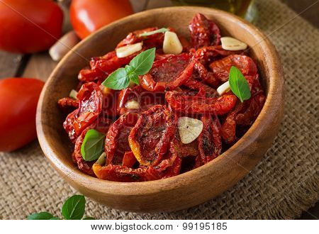 Sun-dried tomatoes with herbs and garlic in wooden bowl
