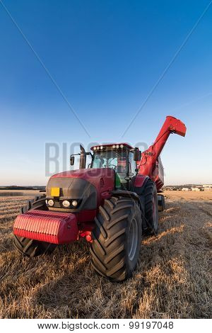 Agriculture Tractor And Trailer On A Stubble Field