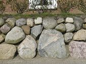 pic of fieldstone-wall  - Frisian stone wall on the Island of Sylt Germany in front of bricks - JPG