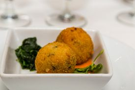 picture of conch  - An appetizer of fresh fried conch fritters and cooked spinach - JPG