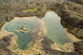stock photo of skinny-dip  - Gran Canaria Banaderos area naturist is bathing in a rock pool shaped like Africa - JPG