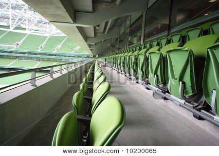 Many rows of green plastic folding seats in a big empty stadium Aviva