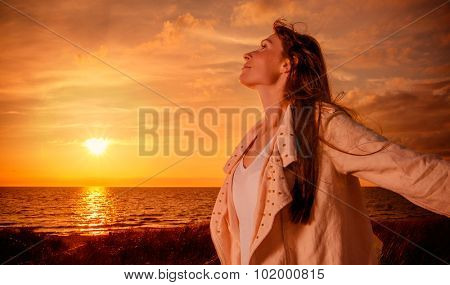 female with outstretched arms in sunset