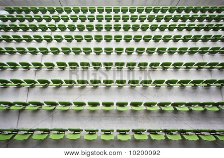Rows of folded green plastic seats in very big empty stadium.