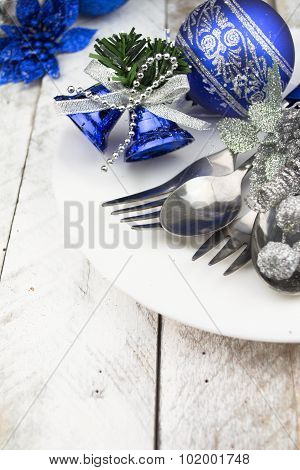 Christmas table setting in silver and blue tone on wooden table