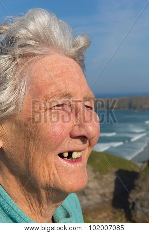 Elderly lady pensioner with dental problems and a tooth missing by beautiful coastal scene