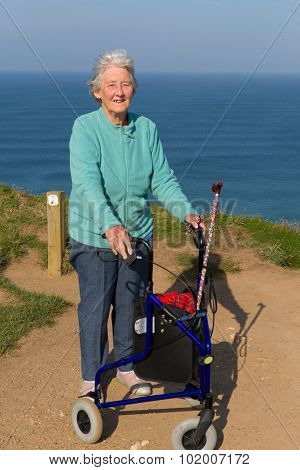 Old lady pensioner with three wheel trolley mobility aid by coast