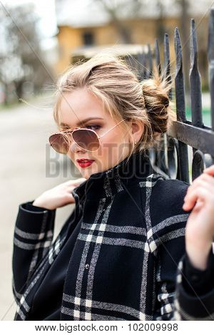Beautiful Woman In Black Coat And Sunglasses Standing Near A Wrought Iron Fence