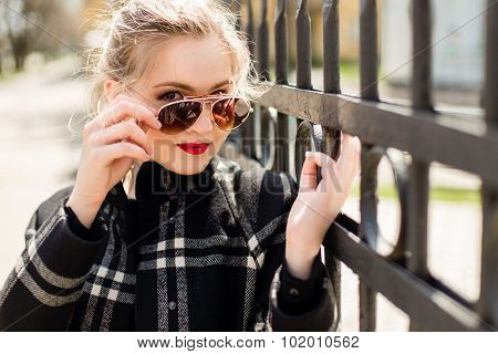 Beautiful Girl In Black Coat And Sunglasses Standing Near A Wrought Iron Fence