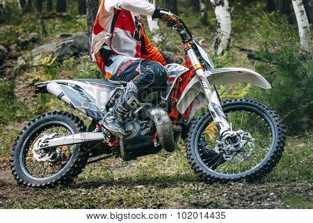 Enduro racer is riding through the woods