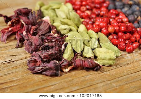a pile of dried hibiscus flowers, green cardamom, pink peppercorns and juniper berries on a rustic wooden table