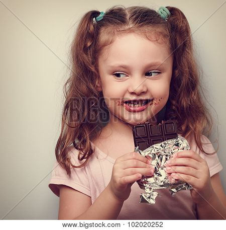 Curious Cute Kid Girl Eating Dark Chocolate And Looking Fun. Closeup Vintage Portrait