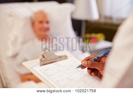 Close Up Of Doctor Writing On Senior Male Patient's Chart