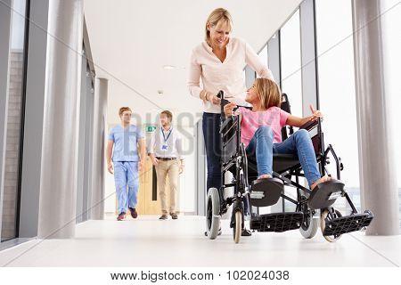 Mother Pushing Daughter In Wheelchair Along Corridor