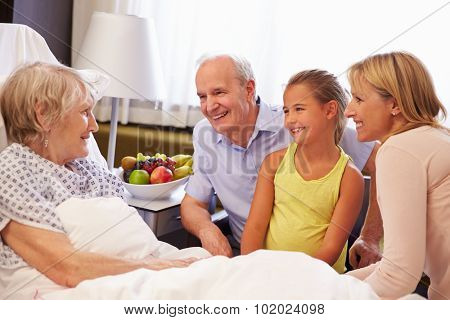 Family Visit To Grandmother In Hospital Bed