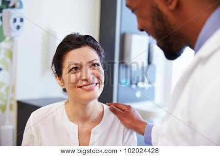 Female Patient Being Reassured By Doctor In Hospital Room