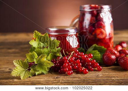 Berries jam in glass jar and wood background