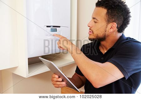 Technician servicing a boiler holding tablet computer