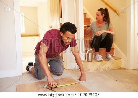 Young homeowners decorating their house