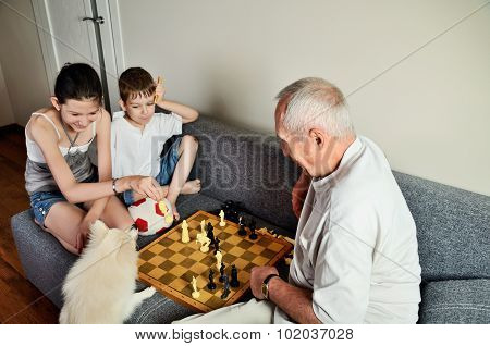 Smiling Grandchildren With Grandpa Playing Chess And Looking At The Dog