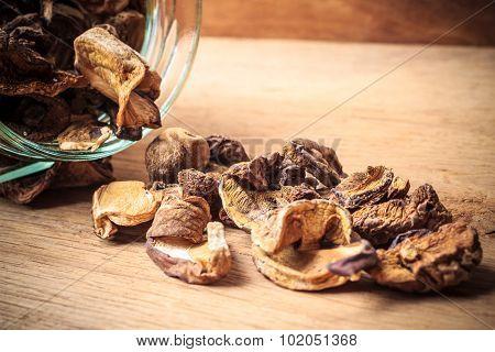 Dry Mushrooms In Jar On Wooden Table.