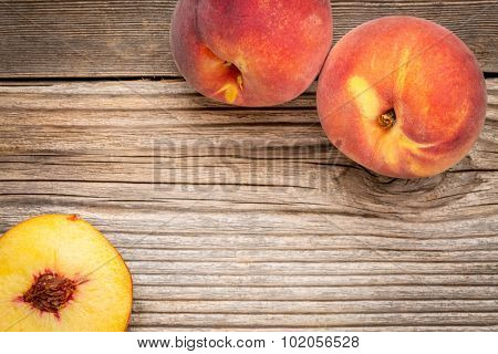 fresh peach fruits on weathered grained cedar wood with a copy space