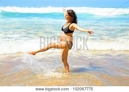 Pregnant woman on the beach at the atlantic ocean