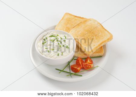 fresh toasts and bowl of chives spread on white plate