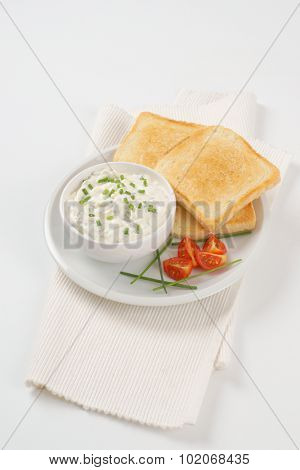fresh toasts and bowl of chives spread on white plate and place mat